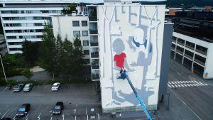 Millo maalaa muraalia Jyväskylässä.