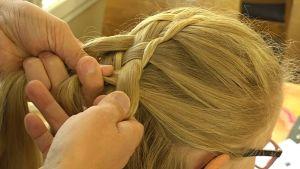 mies letittää tytön hiuksia
