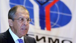 Lavrov kuvattuna vuonna 2014 Ulkosuhteiden instituutissa MGIMO:ssa. Taustalla näkyy instituutin logo, sininen maapallo, jonka edessä on Y:-kirjaimen muotoinen valko-sini-punainen kuvio.