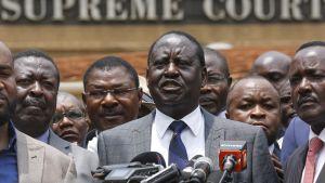 Raila Odinga puhumassa mikrofoniin. Hänen taustallaan seisoo useita saman puolueen poliitikkoja.
