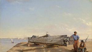 Sukellusvene laiturilla. Mies nojailee aluksen peräisimeen, vieressä istuu kivääriä pitelevä mies.