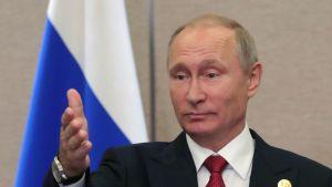 Putin mustassa puvussa, viininpunainen kravatti kaulassaan, takinkauluksessa kullanvärinen merkki. Putin osoittaa oikealla kädellään yleisöön päin, kuin jakaisi puheenvuoroja. Taustalla näkyy Venäjän lippu.