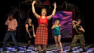 Kaksi miestä ja kolme naista näyttelevät lavalla