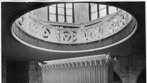 Mustavalkoinen kuva hautakappelissa olevasta vaaleasta sarkofagista.