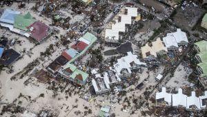 Ilmakuva rannasta: hiekkarantaa, kaikki palmut kaatuneet, taloja sortunut