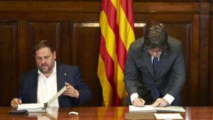 Katalonian aluehallinnon johtaja Carles Puigdemont (oik.) allekirjoittamassa asetusta itsenäisyyskansanäänestyksestä. Vieressä istuu aluehallinnon varajohtaja Oriol Junqueras.