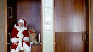 Takavuosien joulukorttisaldoa: joulupukki eduskuntatalon legendaarisessa paternoster-hississä.