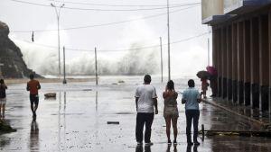 Ihmiset katselevat aaltojen murtumista rantaan havannassa, Kuubassa.