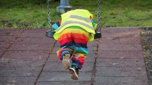 Lapsi keinuu värikkäissä vaatteissa päiväkodin keinussa.