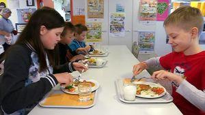 Lapset aterioivat pitkän valkea pöydän ääressä