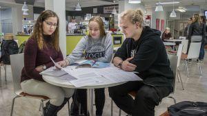 Opiskelijoita koulun kahvilan pöydän ääressä.