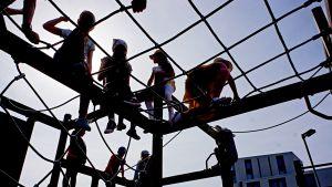 Koululaisia välitunnilla kiipeilytelineen päällä.