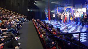 Taidetestaajanuoret teatterin katsomossa ja näyttelijät rivissä näyttämöllä