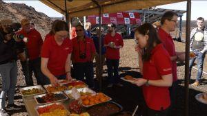 Kokeeseen osallistuneet hedelmä- ja vihannespöydän ääressä Mauna Loan tulivuoren karulla huipulla.