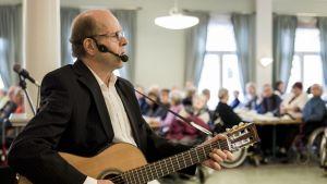 Jouni Kokkoniemi soittaa kitaraa ja laulaa Oulun Aleksinkulmassa.