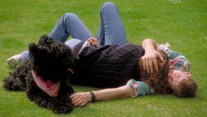 Mies ja nainen makaavat nurmikolla sylikkäin ja musta koira katselee heitä