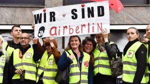 """Airberlinin henkilökuntaa osoittamassa mieltään ja nostamassa kylttiä jossa lukee """"Wir sind Airberlin"""" tänään Berliinissä."""