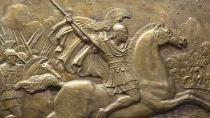 Reliefi, jossa keihästä heiluttava Aleksanteri Suuri johtaa joukkojaan hevosen selässä.