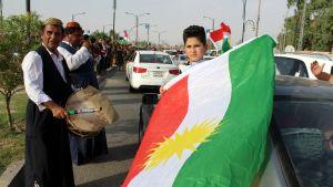 Kurdeja kadulla lippujen ja soittimien kanssa.