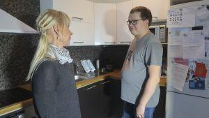 Nuori nainen ja mies modernissa keittiössä.
