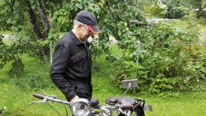 Lippalakkipäinen mies ihailee kevytmoottoripyörää pihalla