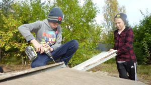 Poika rakentaa scoottiramppia ja käyttää akkuporakonetta.