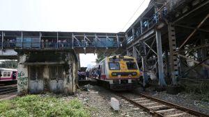 Etualalla juna ja rapistunut rakennus junaraiteiden välissä. Raiteet ylittää jalankulkijoille tarkoitettu silta.