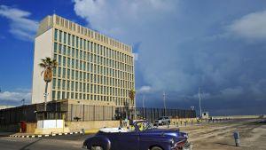 Vanhanmallinen, sininen avoauto ajaa Yhdysvaltain Kuuban suurlähetystön ohi.