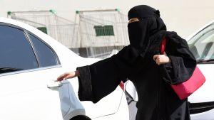 Nainen avaa auton ovea Saudi-Arabiassa.