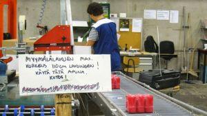Nainen pakkaamassa kynttilöitä tehtaalla