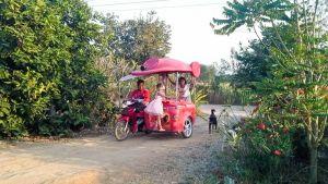 moottoripyöräilijä ja  sivuvaunussa kaksi ihmistä