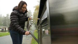 Nainen toppatakissa avaa avaimella postilaatikkoa