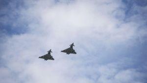 Kaksi hävittäjää lentää pilvistä taivasta vasten.
