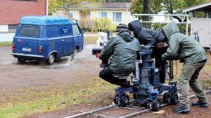 Kuvausryhmä kuvaa lätäkköön ajavaa vanhaa pakettiautoa