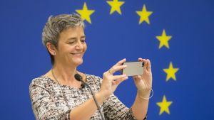 Margrethe Vestager ottaa kuvaa Applen kännykällä. Sinisellä taustalla näkyvät EU:n lipun tähdet.