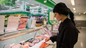 Myyjä käsittelee kalaa kalatiskillä.