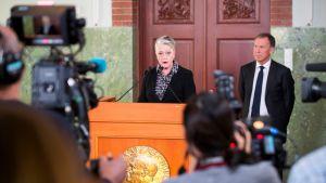 Nainen puhuu mikrofoniin toimittajien ympäröimänä.