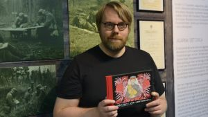 Sarjakuvataiteilija Mika Lietzén pitelee kädessään jääkäriliikkeen historiasta kirjoittamaansa sarjakuva-albumia.