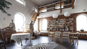 Sisäkuva korkeasta huoneesta jossa portaat nousevat ylös parvelle