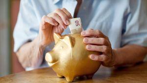eläkeläinen laittaa rahaa säästöpossuun