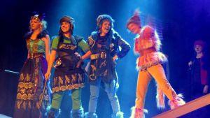 Nejä naista rivissä teatterin lavalla kirkkaissa valoissa