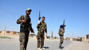kolme maastopukuista sotilasta jalassaan tennarit, käsissään rynnäkkökiväärit.