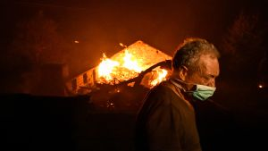 Mies hengityssuojaimen kanssa palavan talon edessä