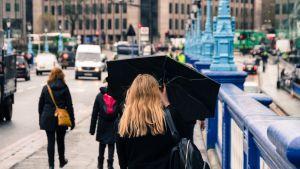 Nainen kuvattuna Lontoon kadulla sateenvarjo kädessään.