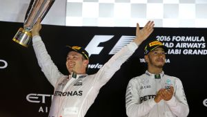 Nico Rosberg (vas.) ja Lewis Hamilton palkintokorokkeella. Rosberg tuulettaa pokaali kädessään. Hamilton taputtaa vieressä.