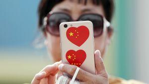 Kiinalainen nainen tutkii kännykkäänsä.