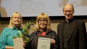 Kaksi naista ja mies hymyilevät kunniakirjan kanssa.