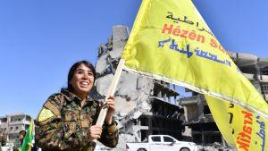 Syyrian demokraattisten joukojen (SDF) komentaja Rojda Felat kulkee lippua kantaen Raqqassa.