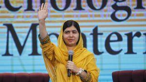 Malala Yousafzai tervehtii kättään nostaen. Toisessa kädessä on mikrofoni.