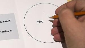 Käsi kirjoittamssa äänestysnumeroa äänestyslipukkeeseen.